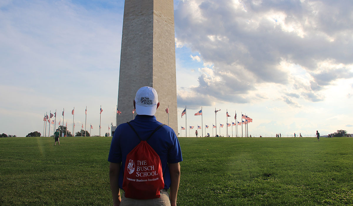 Student wearing Busch School of Business hat and backpack in front of Washington Monument