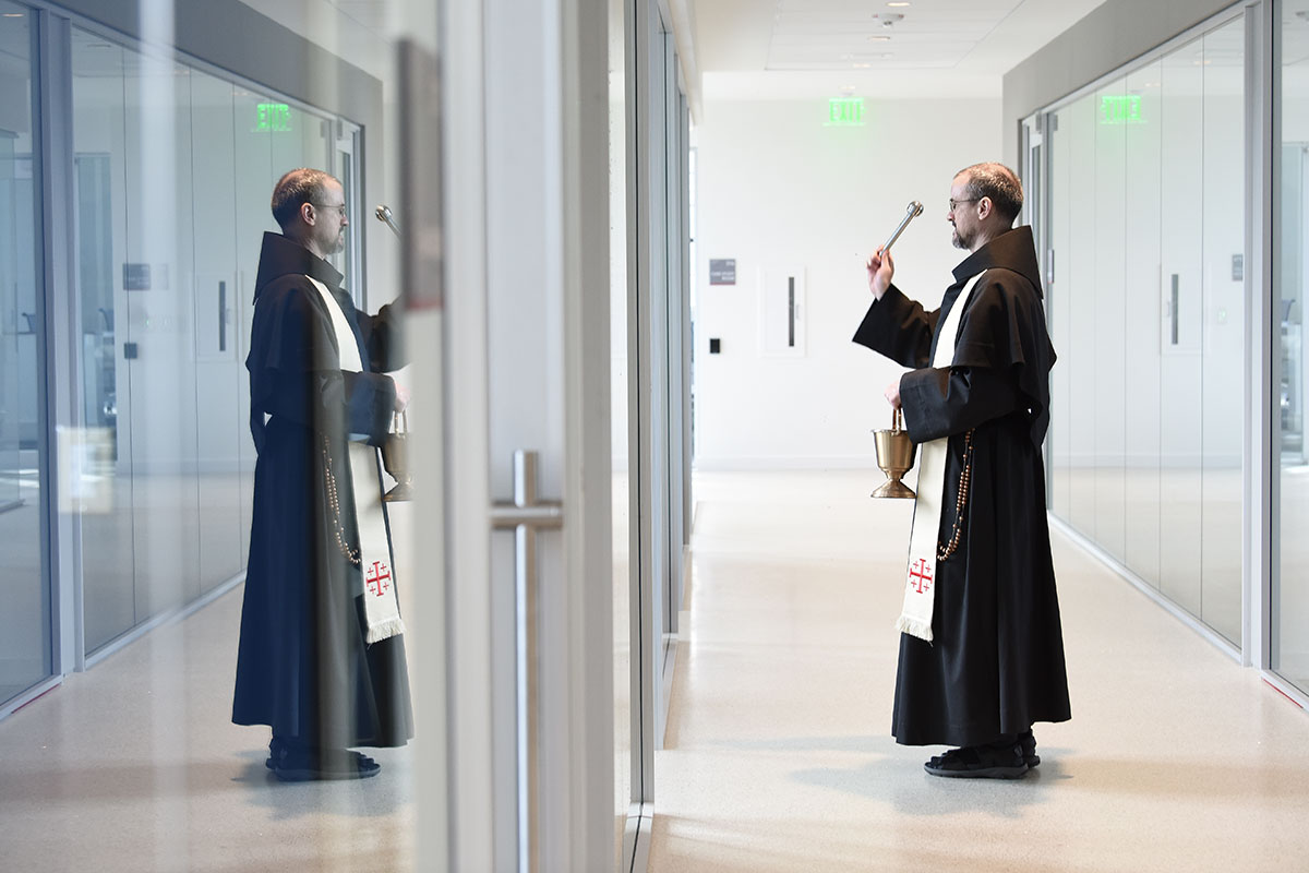 Priest blessing rooms in a building