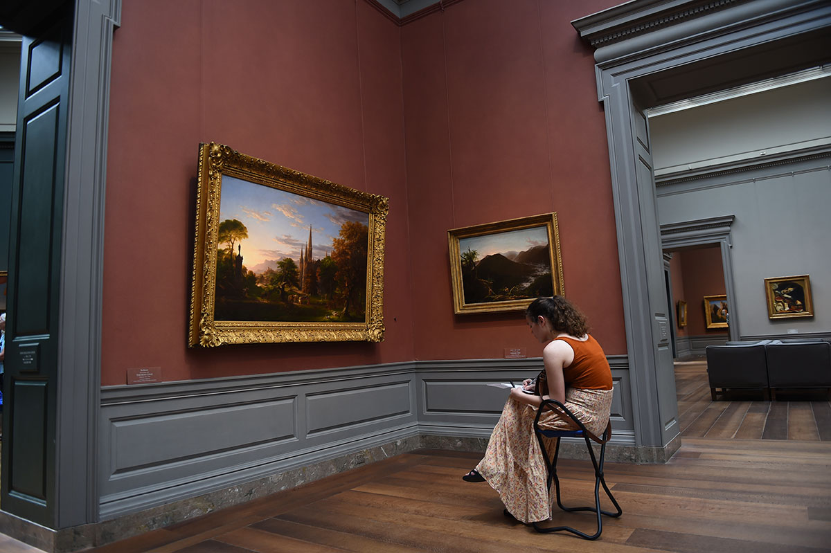 Student sitting on chair in art museum, looking at artwork and drawing