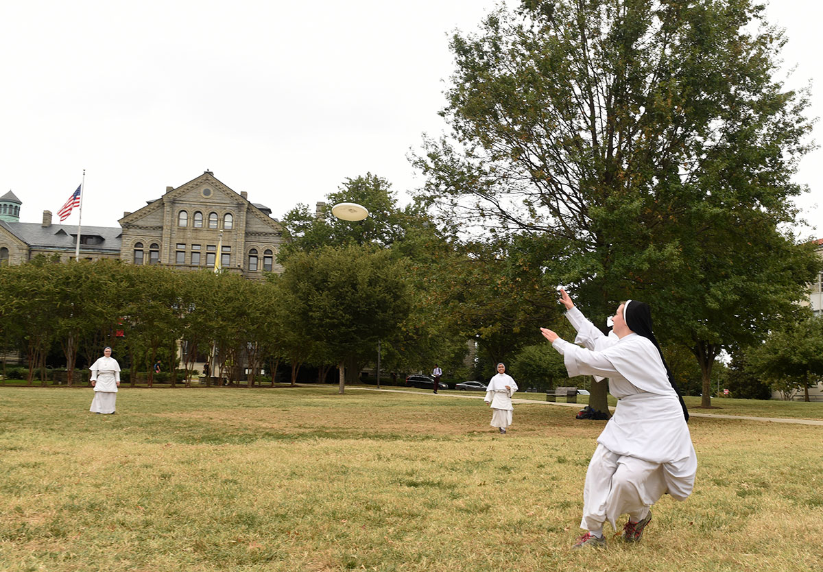 A group of religious sisters playing Frisbee on the lawn in front of McMahon Hall during lunchtime.