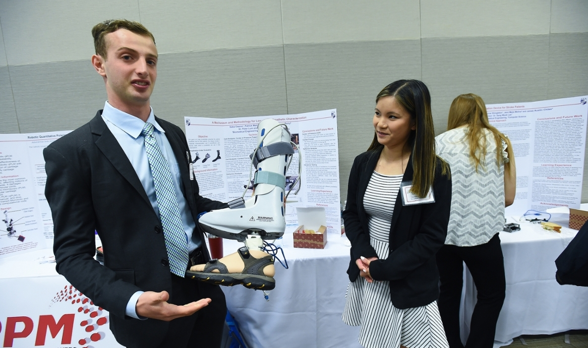 Engineering students showing prosthetic leg the developed