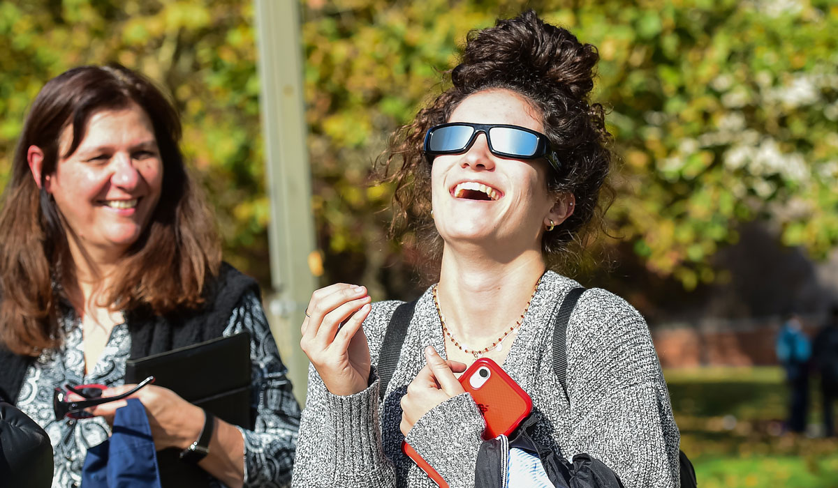 Female student looking at Mercury through sunglasses
