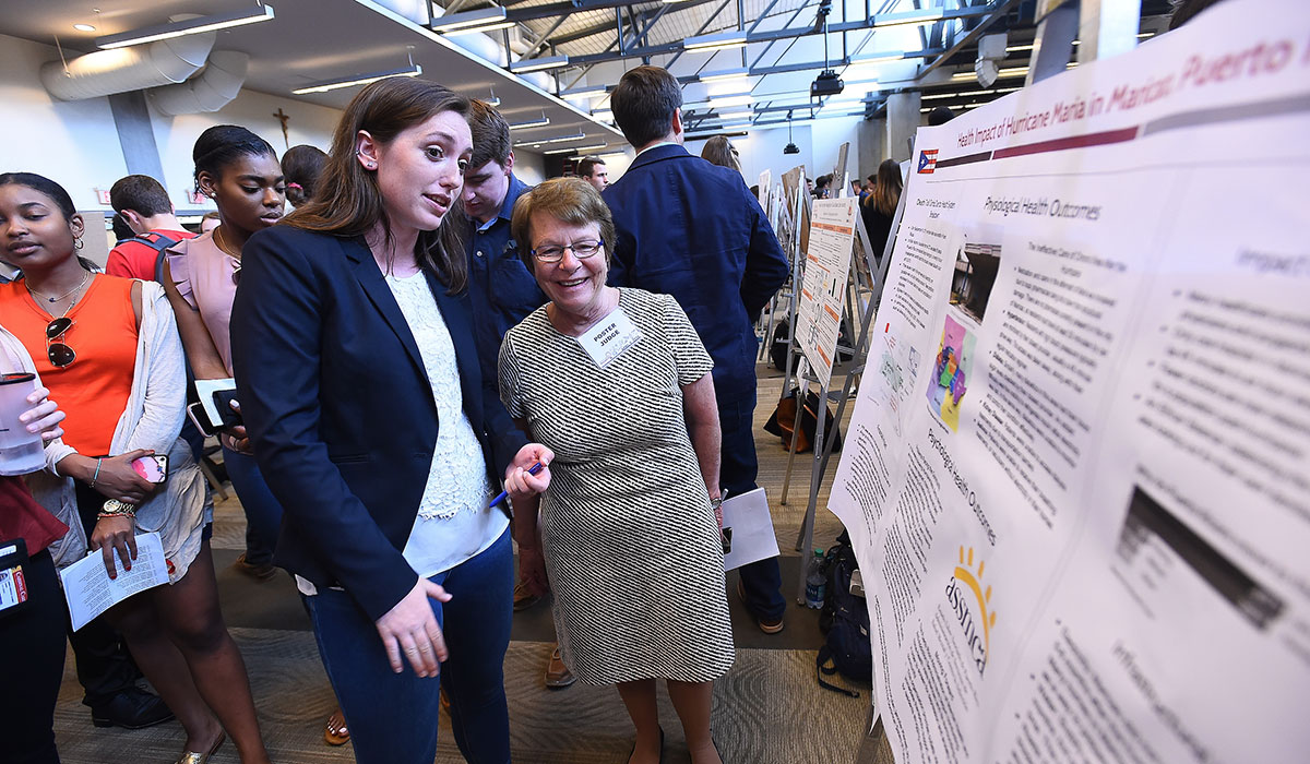Female student presents her poster to Nursing Dean Pat McMullen