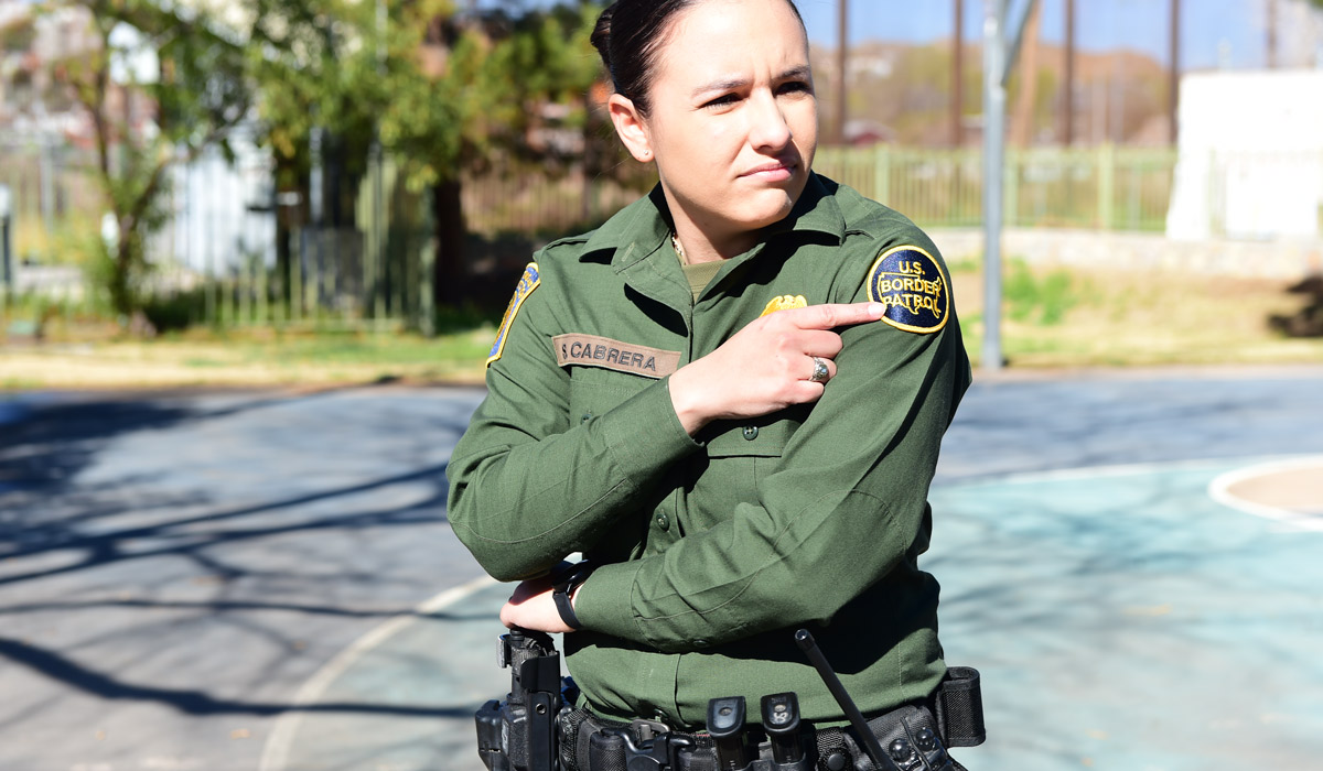 Border Patrol Agent Sara M. Cabrera point to a patch on her uniform.