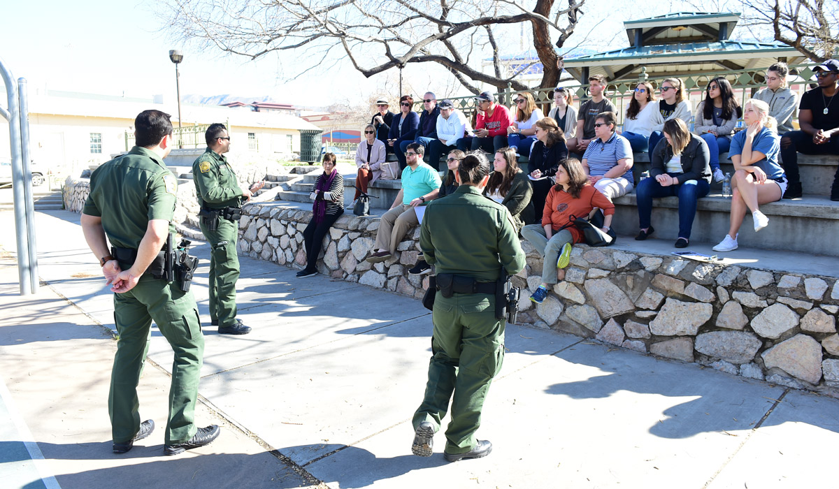 Students and staff listen to presentation by three U.S. Border Patrol officers