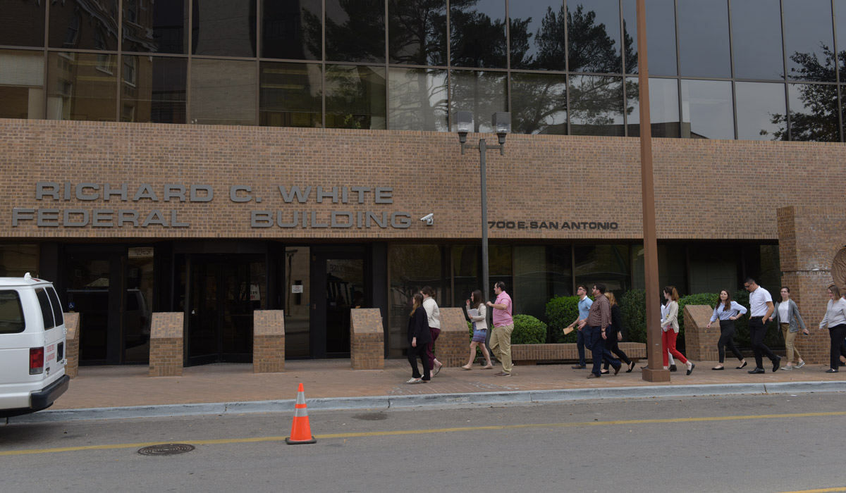 A groups of people walking in front of the Federal Courthouse in El Paso.