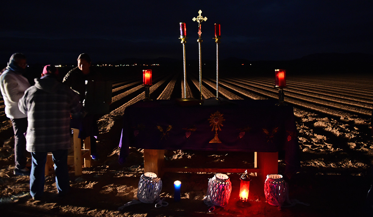 An altar set up in the dark on an onion field.