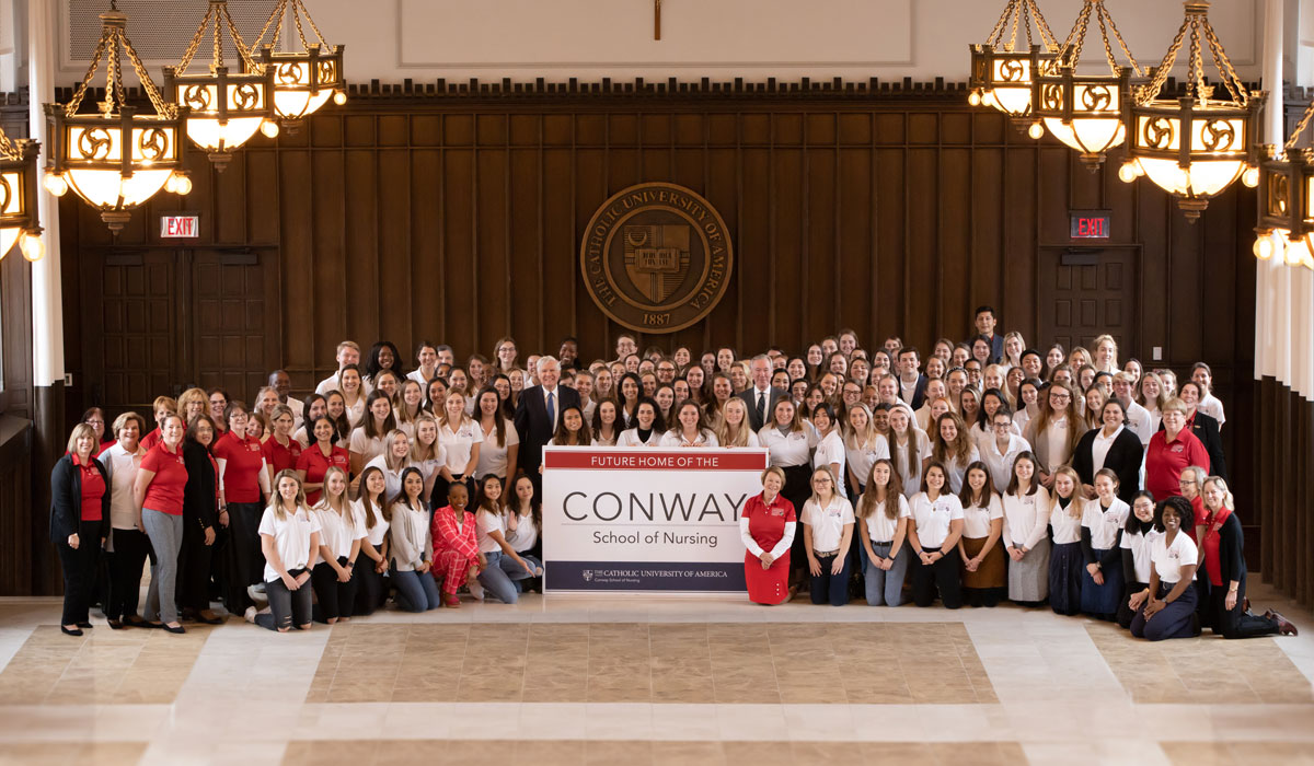 Group photo of Bill Conway with Nursing Dean Pat McMullen and nursing school students