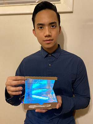 "Marshall Mendoza displays his design project, the ""De-Coronizer 7000,"" a portable box which cleans face masks using a UV light."