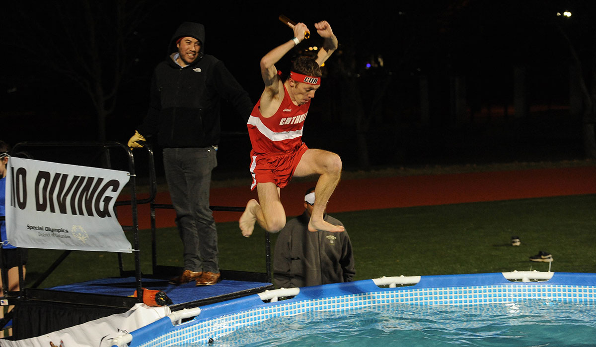Athlete jumping into pool of cold water
