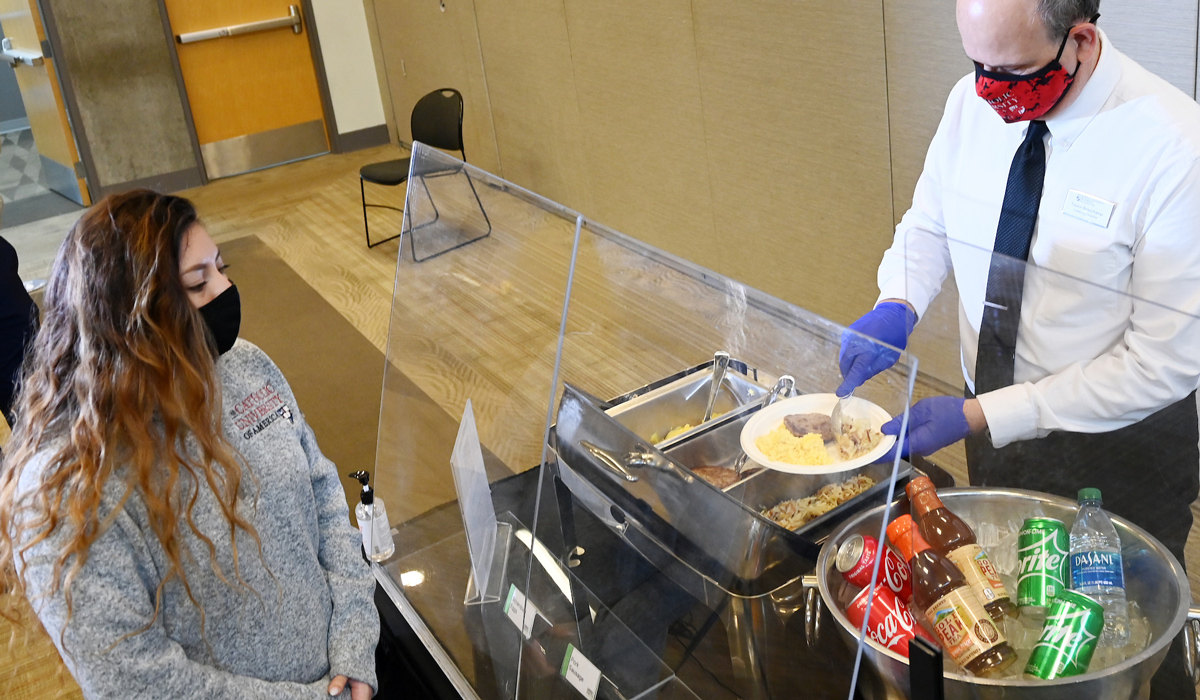 Contactless catering on campus shows server behind plexiglass shield
