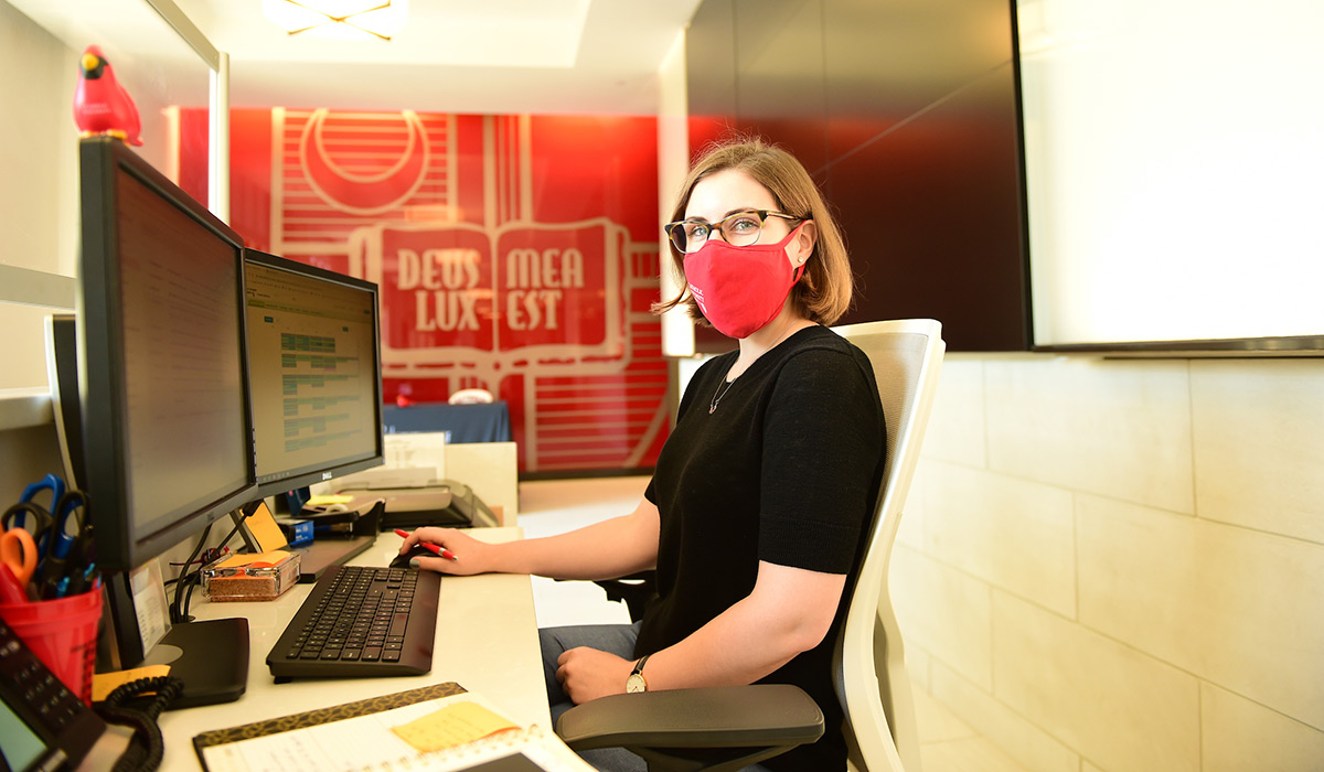 Female employee working at computer while wearing a mask