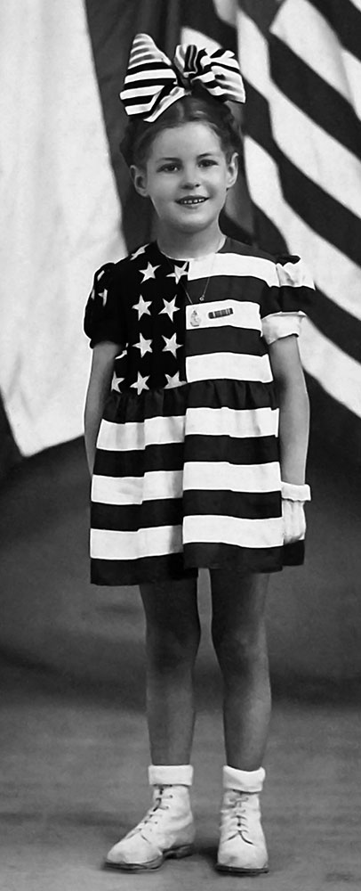 A black and white image of a little girl in an American flag dress