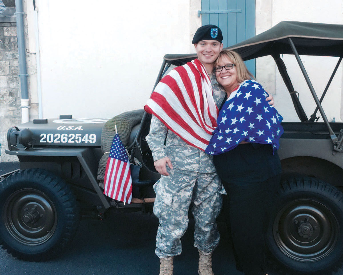 American soldier and his mother draped in an American flag standing in front of a military Jeep