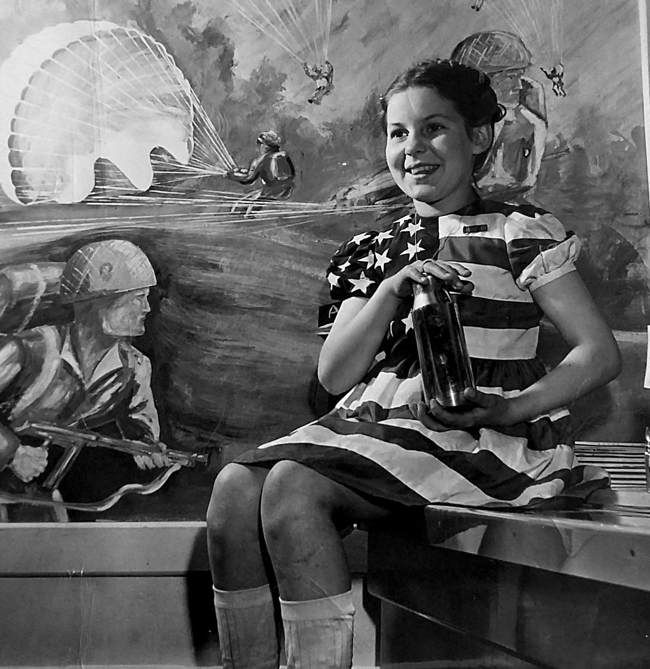 A black and white photo of a girl wearing an American flag dress