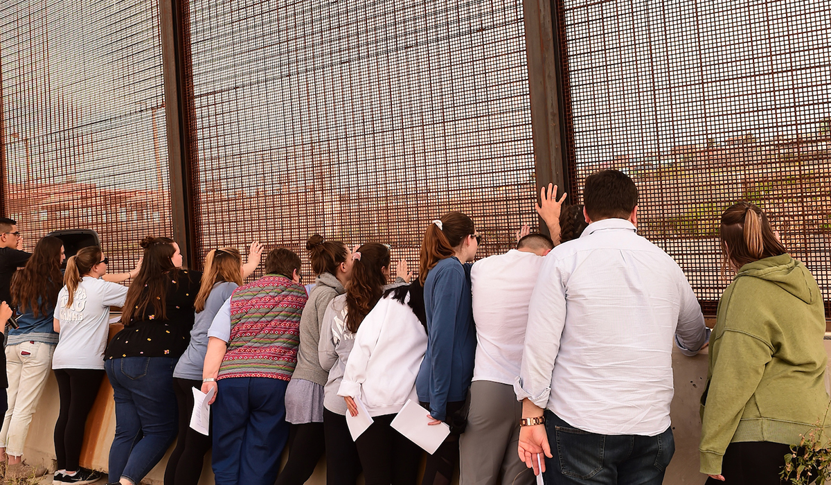 Students putting their hands on border fence