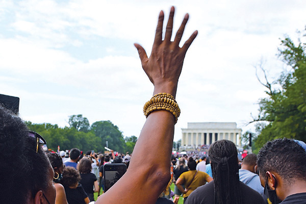 Woman holding her hand up in the air at a protest