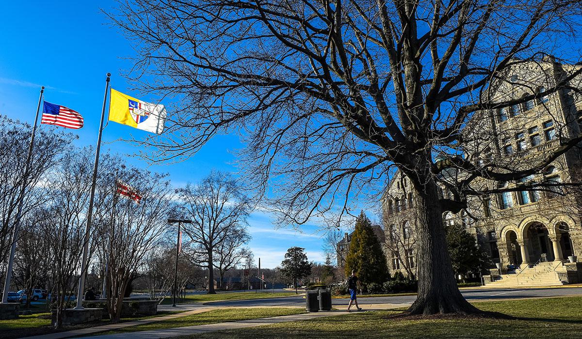 Student walking across campus toward McMahon Hall