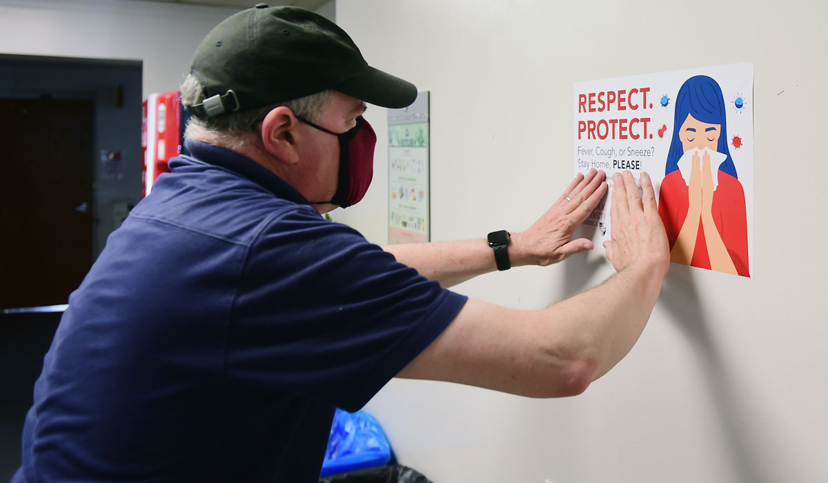 Facilities staff member posting Respect. Protect. sign on wall.