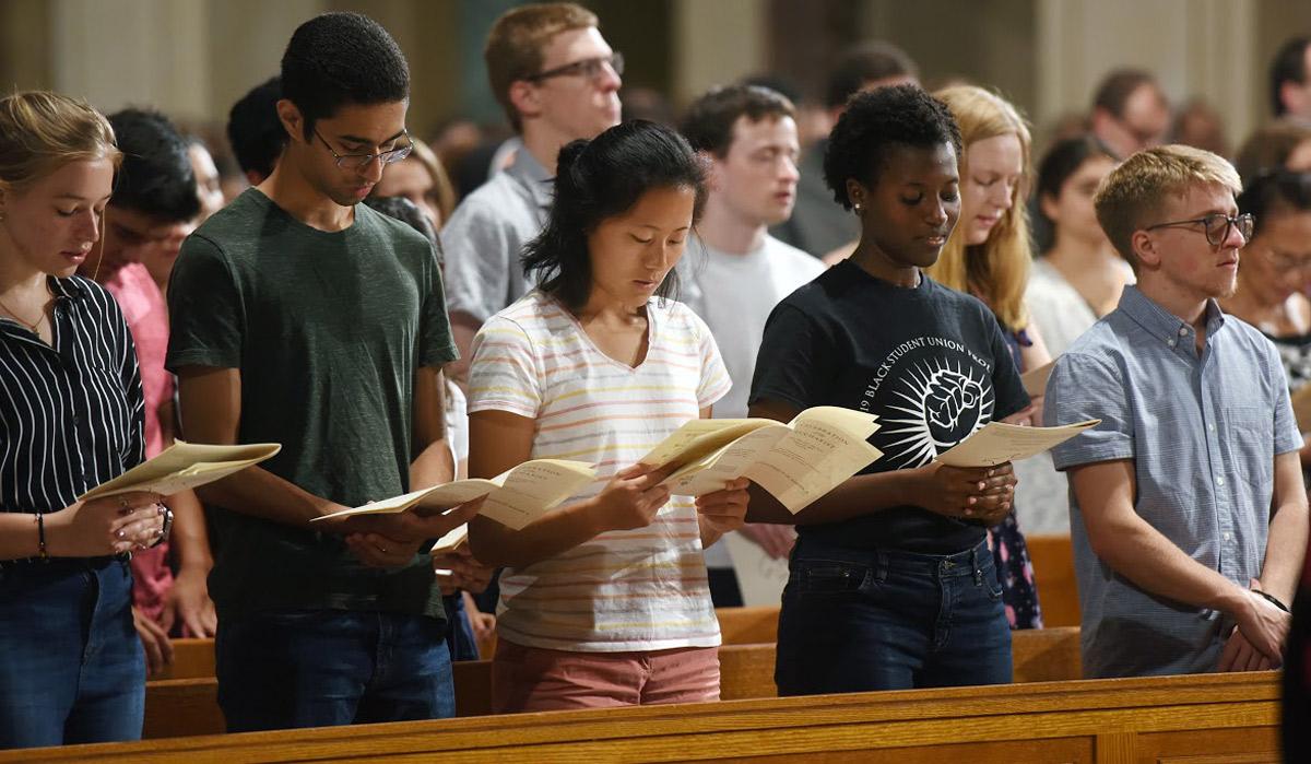 students praying at Mass