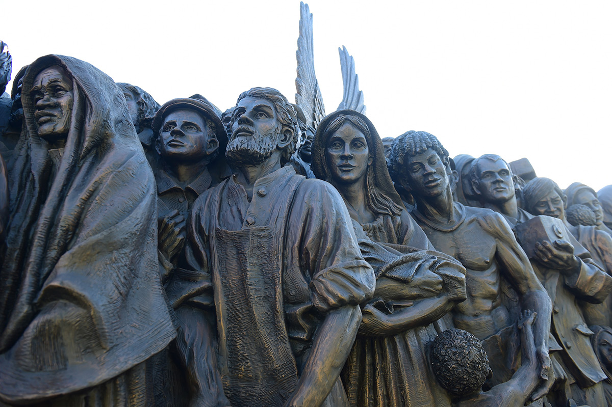 Close up of statue featuring the faces of migrants and refugees