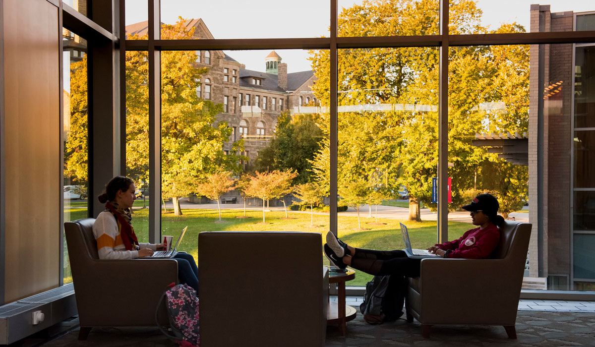 Students sitting in chairs, using laptops, next to a window overlooking yellow trees on campus