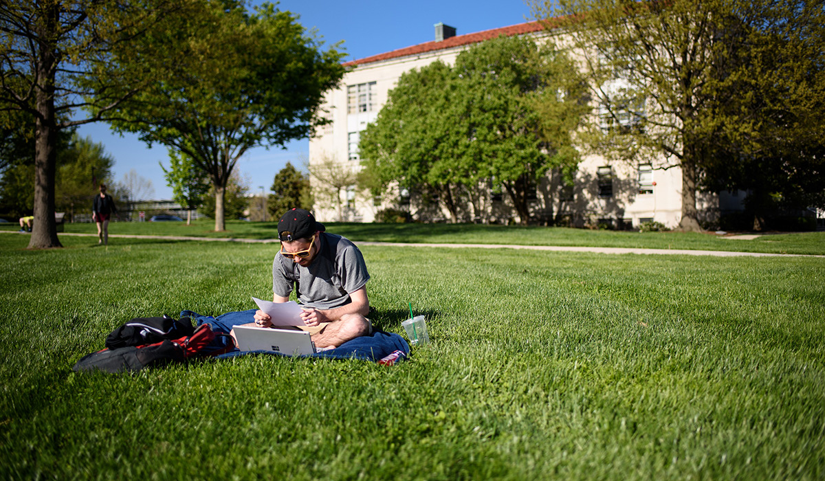 Student sitting on lawn with his laptop