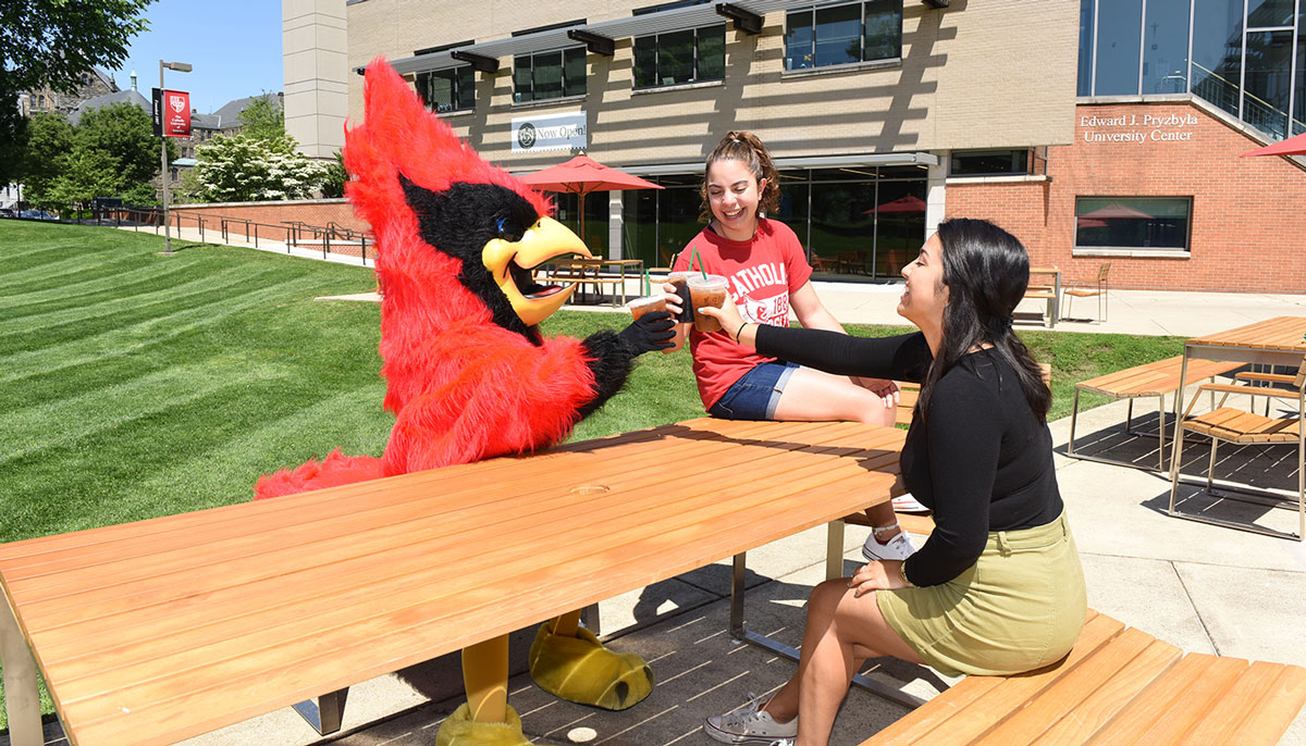 Students sitting with Red the mascot