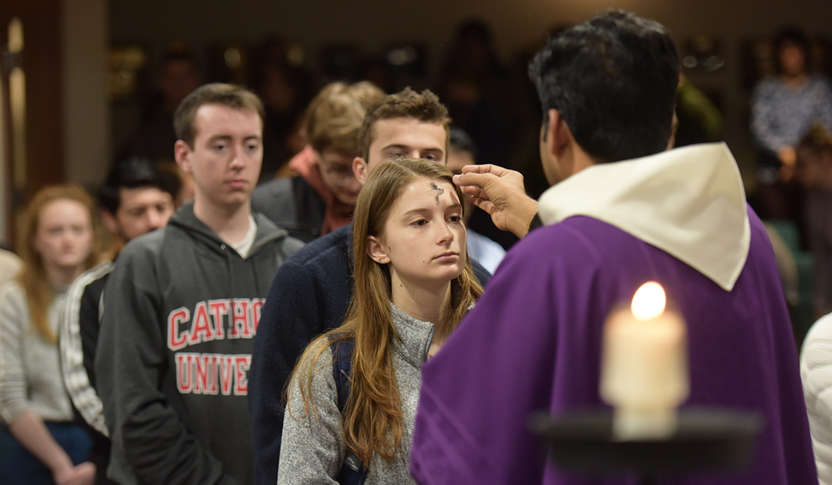 Priest putting ashes on a student's head