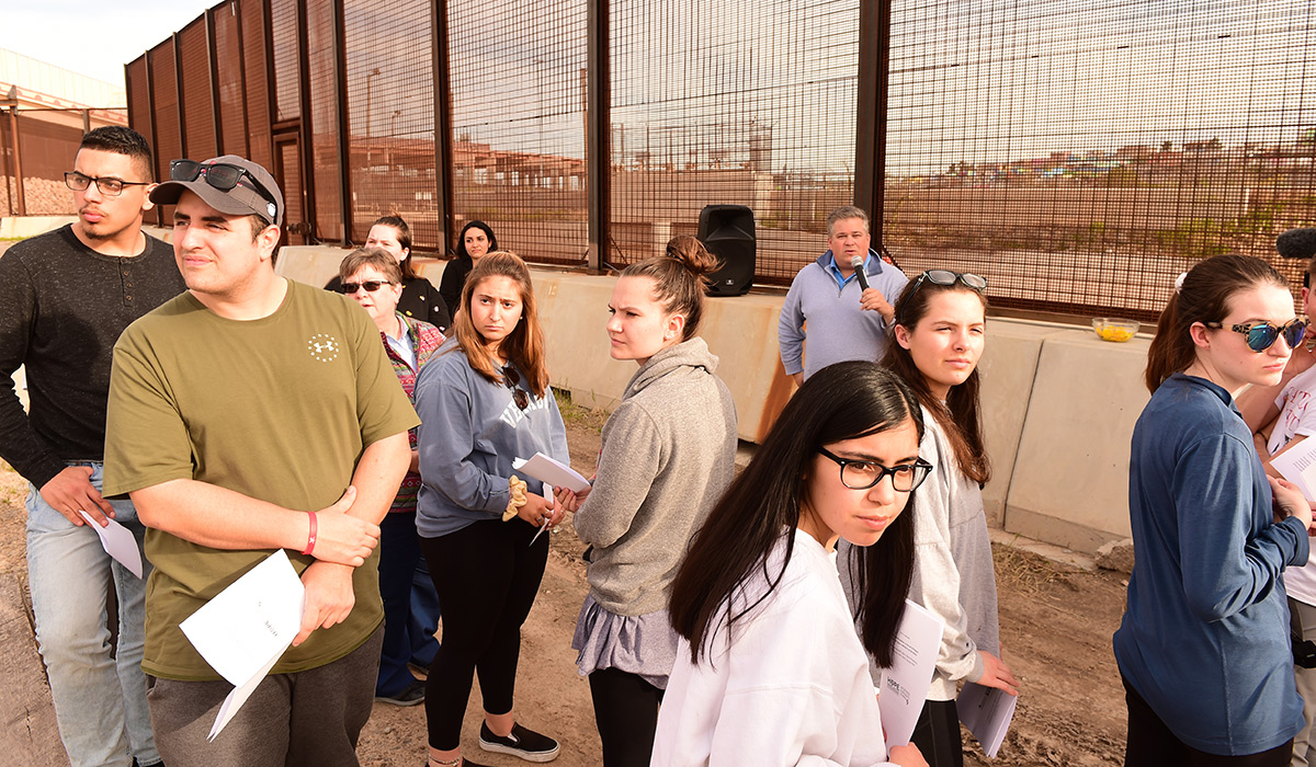 Students looking around with the border fence behind them