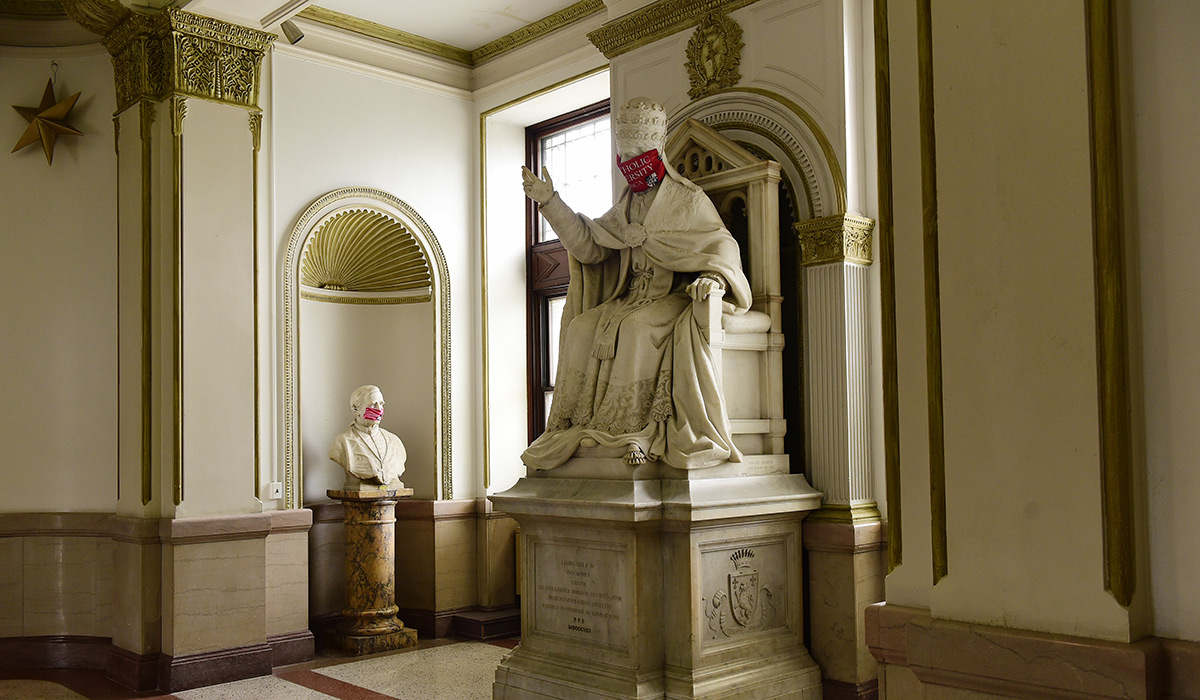 Pope Leo statue with a mask on its face