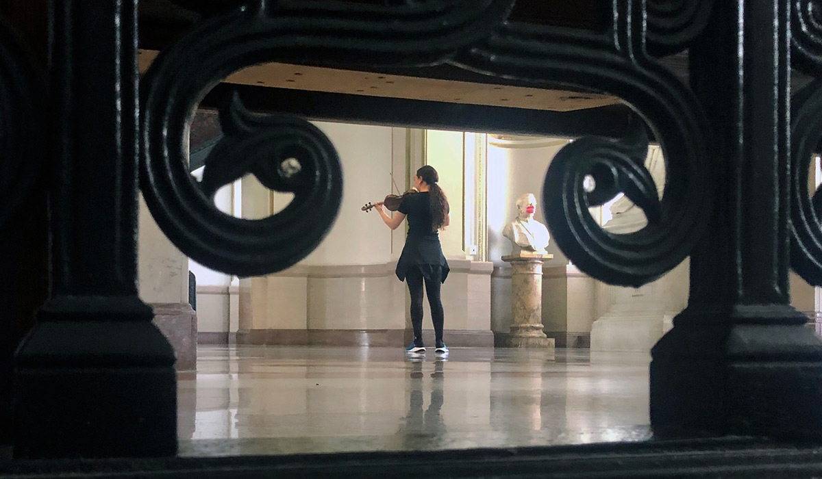 Student playing violin in the lobby of McMahon Hall