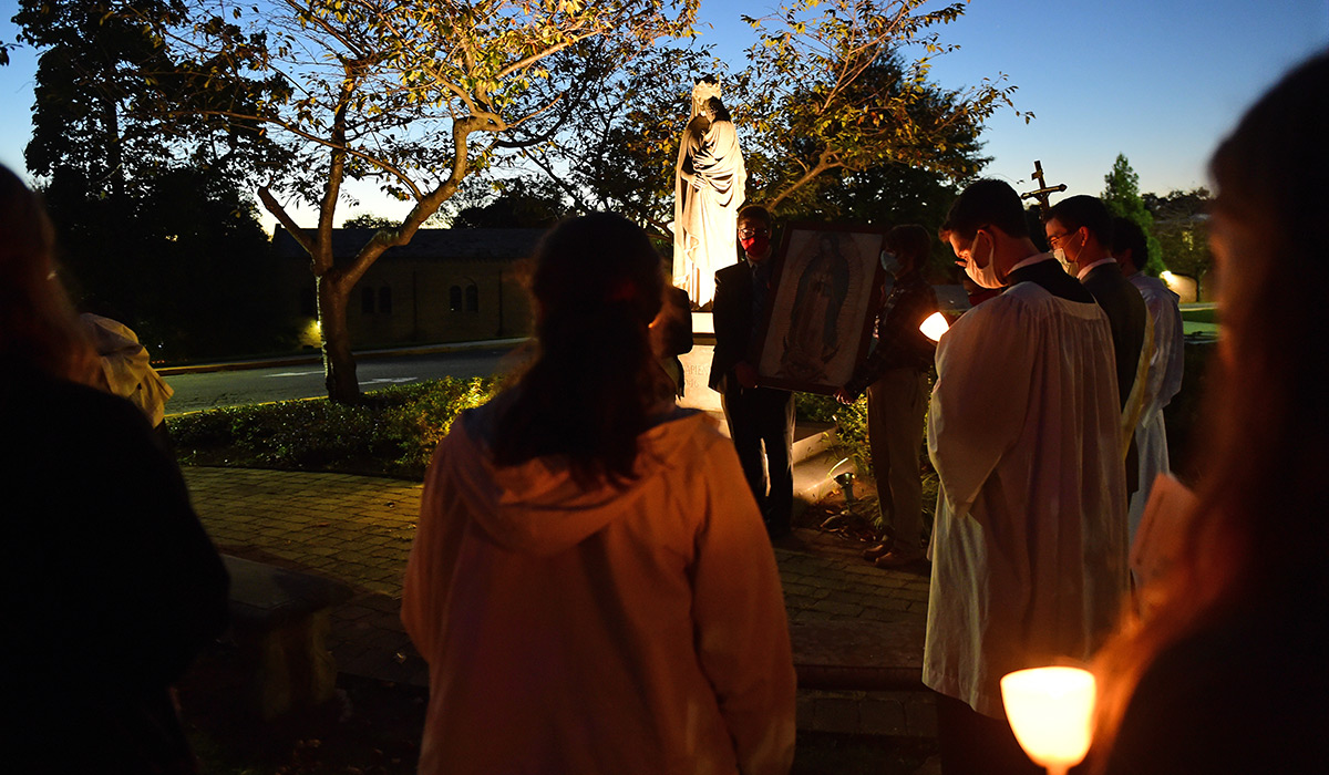 Students with candles around a statue of Mary