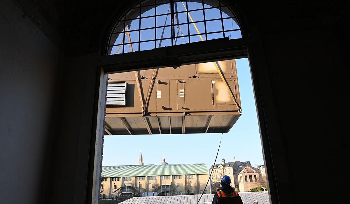 A crane lifts a mechanical unit as seen through a window