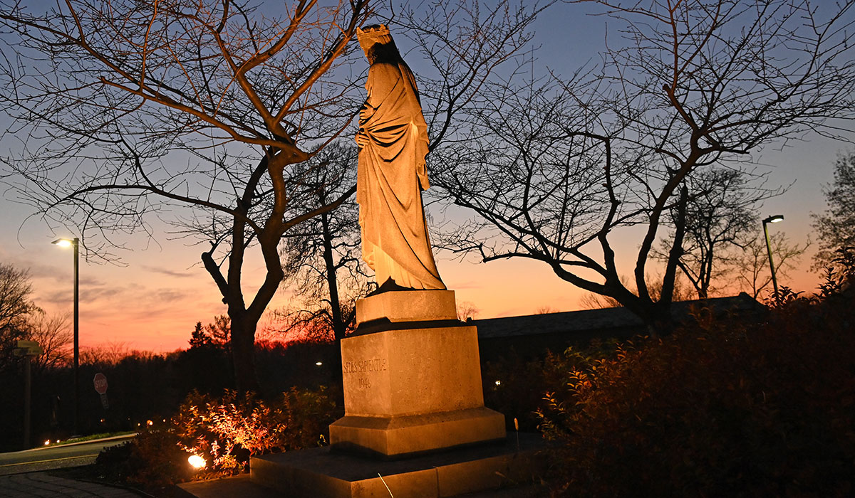 Mary, Seat of Wisdom statue with sun setting behind it.