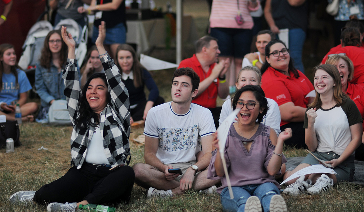 Students sitting on the lawn during a campus event