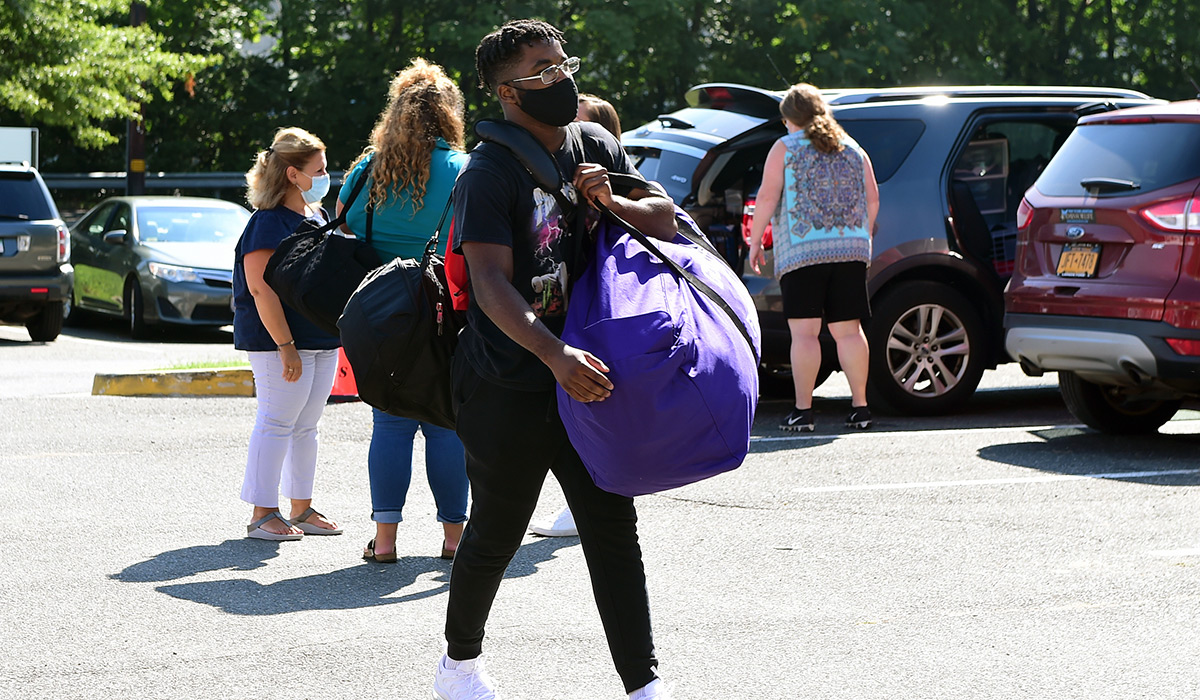 A male student carries a bag into a residence hall