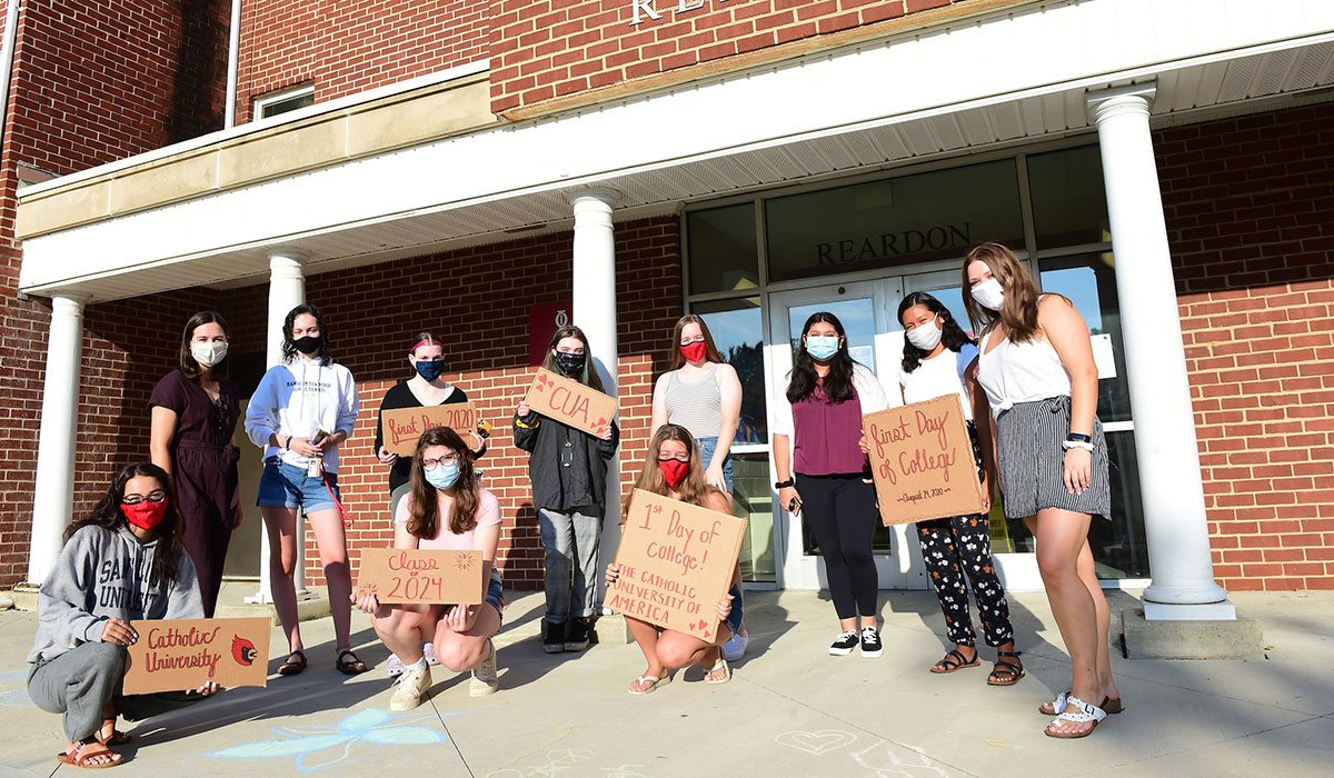 Students pose with signs to celebrate their first day of school