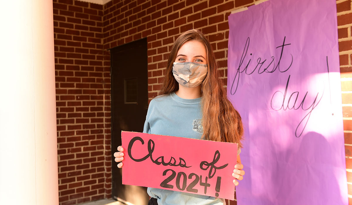 Female student with a Class of 2024 sign