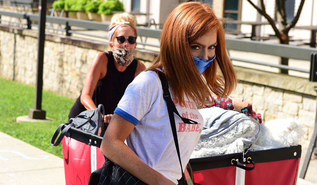Female student peering over top of mask as she carries in belongings