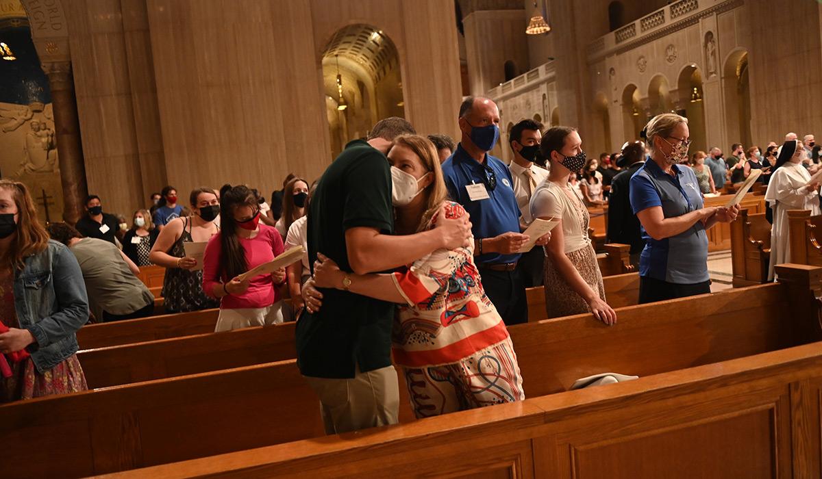 Parent hugging their child at Mass