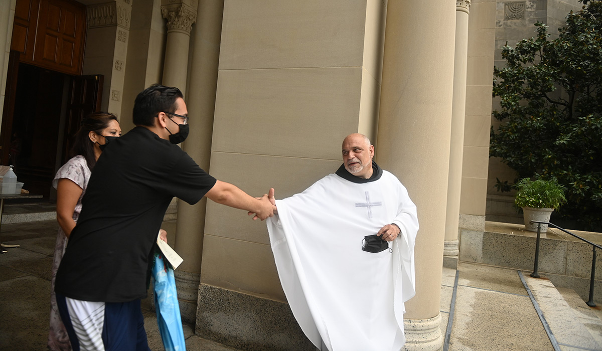 University chaplain shakes hands with student