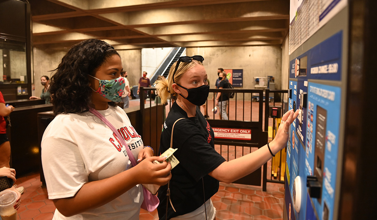 Student learning how to use Metro fare card machine