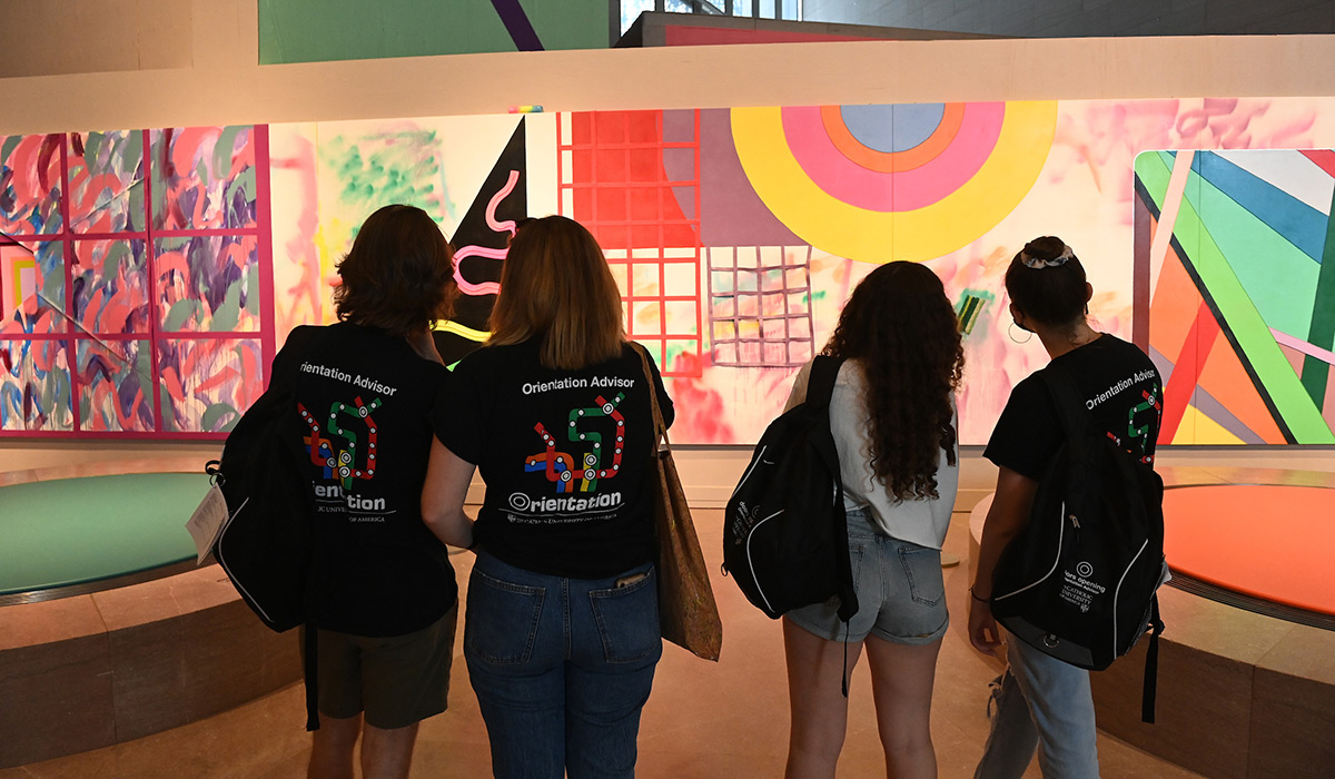 Students admiring a colorful mural