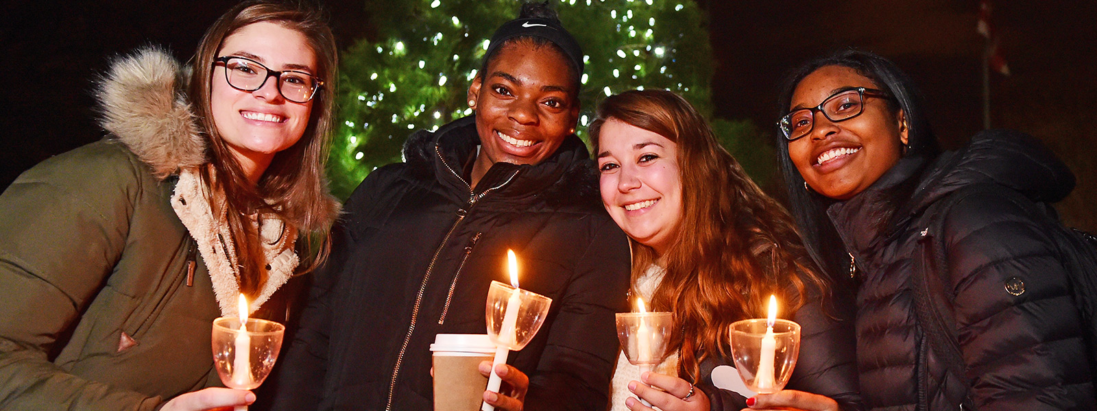 Female students holding candles in front of lit Christmas tree