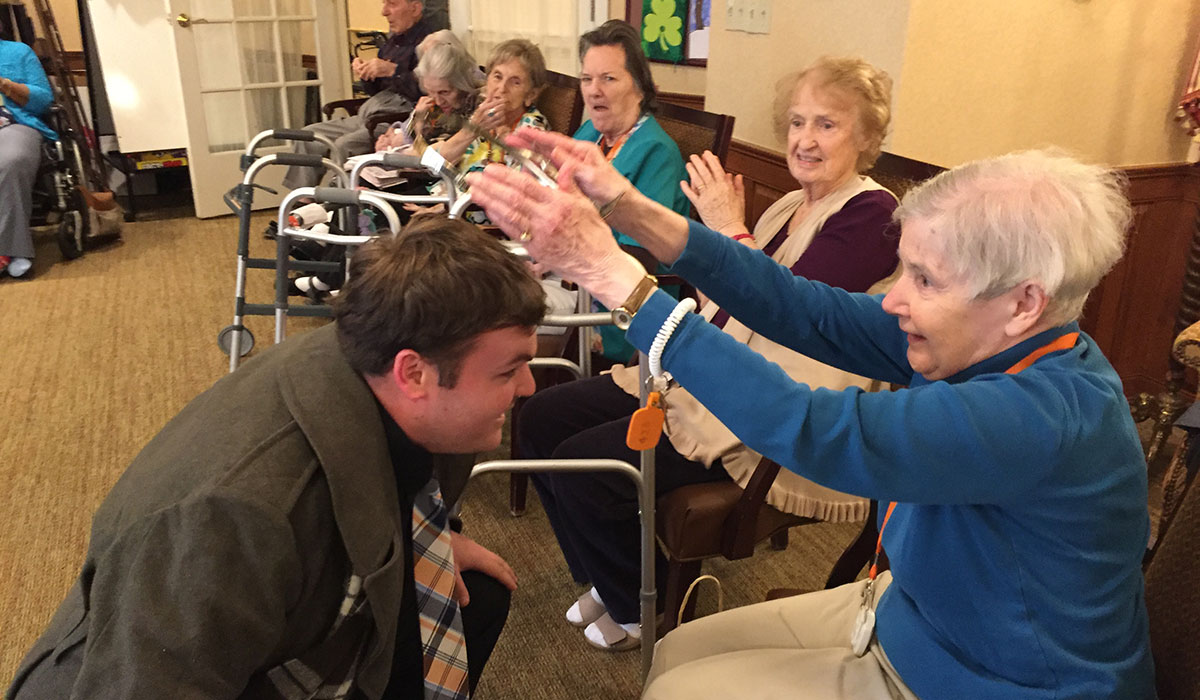 Kevin Boudreau, M.F.A. acting candidate who plays Malcolm in Macbeth, is crowned by a resident of Sunrise Assisted Living